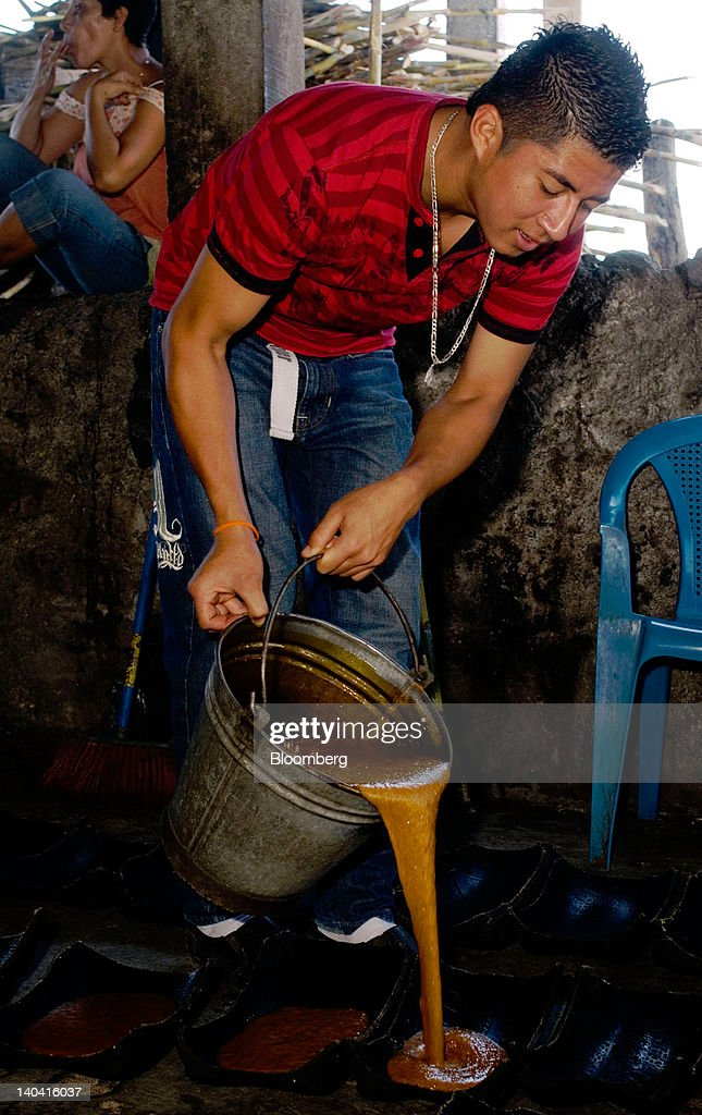 A worker pours a hot mass of juice concentrate into molds to make handmade panela, a solid piece of unrefined whole cane sugar obtained from the boiling and evaporation of sugarcane juice, at a traditional sugar mill in Tepetitan, El Salvador, on Sunday, Feb. 26, 2012. Global sugar supply will be 'under pressure' amid significant demand growth by 2020, which may push prices up further, according to Mannheim, Germany-based refiner Suedzucker AG. Photographer: Juan Carlos/Bloomberg via Getty Images