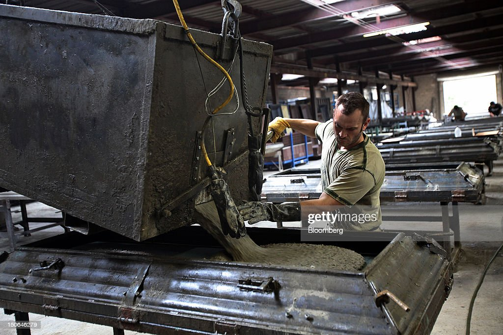 A worker pours concrete for a burial vault cover at the American Wilbert Vault Corp. manufacturing facility in Des Plaines, Illinois, U.S., on Thursday, Aug. 23, 2012. Several U.S. Presidents including John F. Kennedy and Ronald Reagan, and other famous people including Al Capone, Louis Armstrong, Elvis Presley and Frank Sinatra are buried in American Wilbert burial vaults, according to the company. The U.S. Census Bureau is expected to release data on orders for durable goods on Aug. 24. Photographer: Tim Boyle/Bloomberg via Getty Images