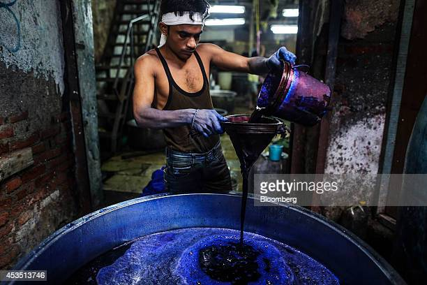 A worker pours dye into a metal vat while preparing to dye fabric in a workshop in the Dharavi slum area of Mumbai India on Monday Aug 11 2014 Almost...