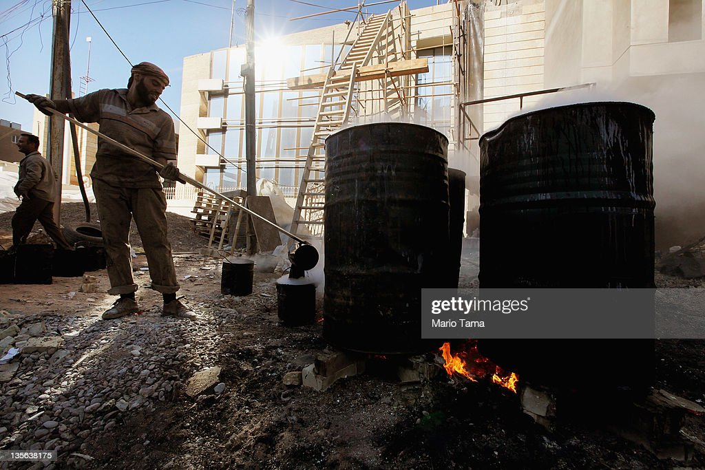 A worker pours hot tar to be used on a roof on December 12, 2011 in Baghdad, Iraq. Iraq is transitioning nearly nine years after the 2003 U.S. invasion and subsequent occupation. American forces are now in the midst of the final stage of withdrawal from the war-torn country. At least 4,485 U.S. military personnel have died in service in Iraq. According to the Iraq Body Count, more than 100,000 Iraqi civilians have died from war-related violence.