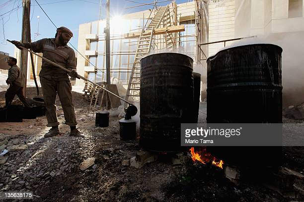 A worker pours hot tar to be used on a roof on December 12 2011 in Baghdad Iraq Iraq is transitioning nearly nine years after the 2003 US invasion...