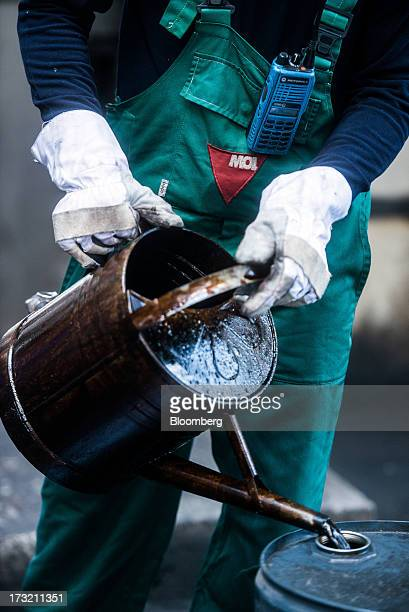 A worker pours liquid oil from a can into a barrel at the delayed coker unit of the Duna oil refinery operated by MOL Hungarian Oil and Gas Plc in...