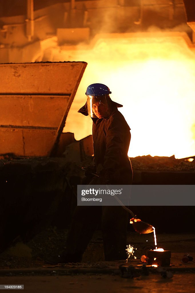 A worker pours molten cast iron he has collected from a furnace at the OAO Novolipetsk Steel plant, also known as NLMK, in Lipetsk, Russia, on Wednesday, Oct. 17, 2012. OAO Novolipetsk Steel, controlled by billionaire Vladimir Lisin, became Russia's largest steelmaker by output after boosting production by 24 percent. Photographer: Andrey Rudakov/Bloomberg via Getty Images