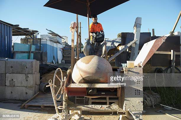 A worker pours water into a concrete mixer at the yard of Gully Concrete supplies in Melbourne Australia on Tuesday Aug 16 2016 Australia's economy...