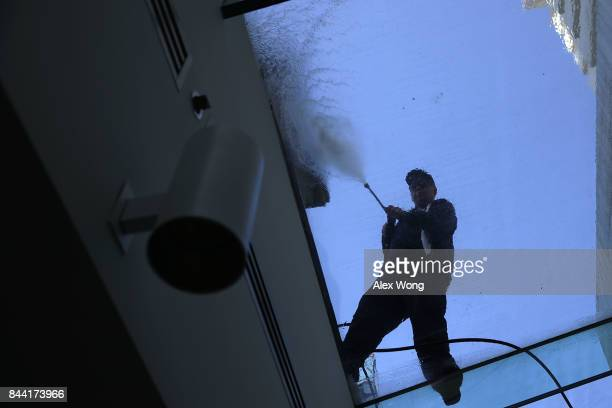 A worker powerwashes a glass ceiling during a House Republican Conference meeting on September 8 2017 at the Capitol in Washington DC Secretary of...