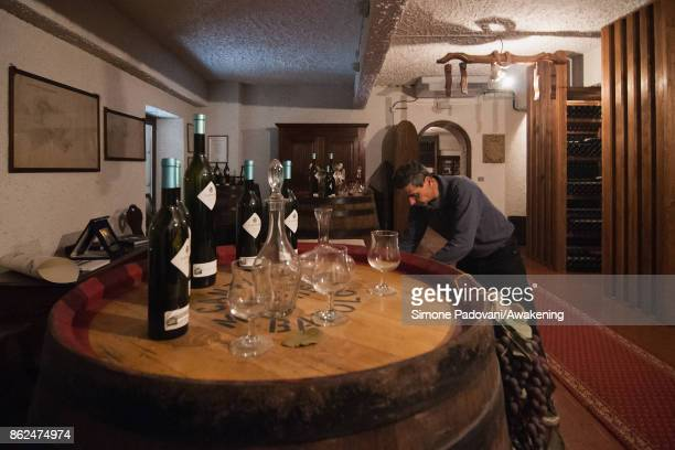 A worker prepare the tasting of Barolo for some visitors on October 17 2017 in the Barolo region Italy Because of the high summer temperatures...