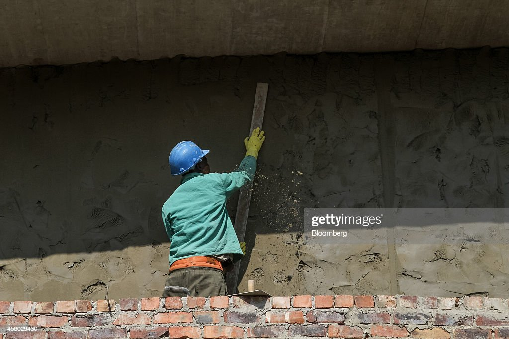 A worker prepares a cement wall covering at the Capital Hill office construction site in Sandton South Africa on Tuesday Sept 23 2014 Sandton once a...