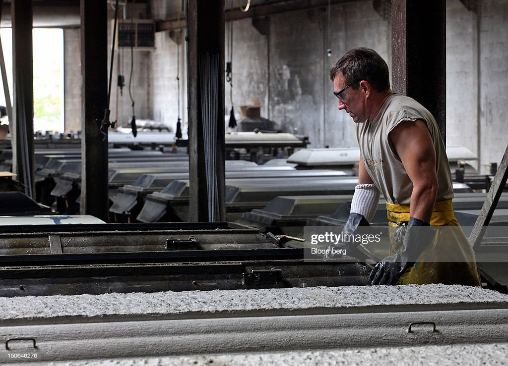 A worker prepares a concrete form for a burial vault cover at the American Wilbert Vault Corp. manufacturing facility in Des Plaines, Illinois, U.S., on Thursday, Aug. 23, 2012. Several U.S. Presidents including John F. Kennedy and Ronald Reagan, and other famous people including Al Capone, Louis Armstrong, Elvis Presley and Frank Sinatra are buried in American Wilbert burial vaults, according to the company. The U.S. Census Bureau is expected to release data on orders for durable goods on Aug. 24. Photographer: Tim Boyle/Bloomberg via Getty Images