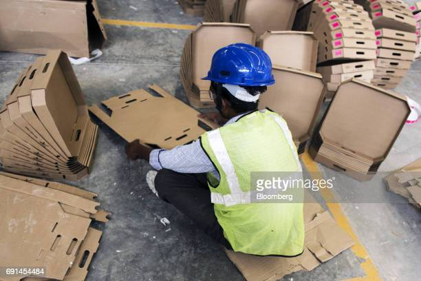 A worker prepares cardboard packing trays at an Akzo Nobel India Ltd paint factory in Gwalior Madhya Pradesh India on Thursday June 1 2017 Akzo Nobel...