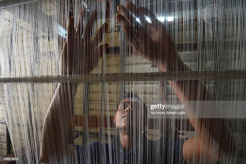 A worker prepares fibres to be used in the making of silk fabrics on a loom on December 21, 2013 in Bogor, Indonesia. The Indonesian silk industry is well established although generally consisting of small and local producers in contrast to more developed competition and industry seen in countries such as Japan, China and Thailand. The silk produced is used in the manufacture of traditional handicrafts including batik clothing and textiles.