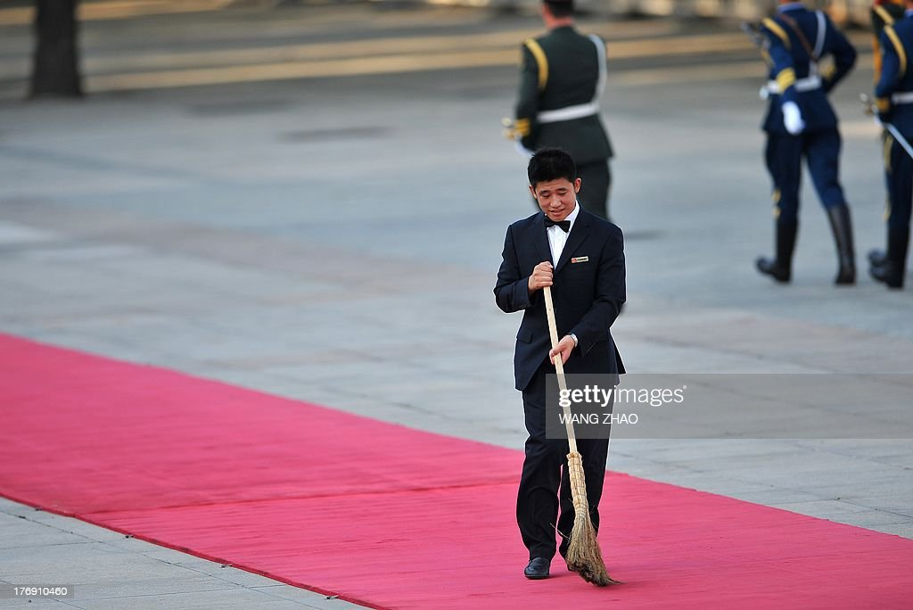 A worker prepares for the arrival of Kenya's President Uhuru Kenyatta and Chinese President Xi Jinping during a welcoming ceremony outside the Great Hall of the People in Beijing on August 19, 2013. Uhuru Kenyatta is on a visit to China from August 18 to 23. AFP PHOTO / WANG ZHAO