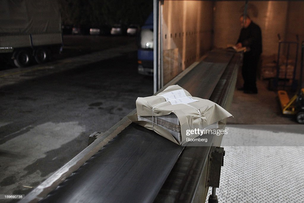 A worker prepares packaged bundles of the International Herald Tribune in the distribution area of the Kathimerini printing plant in Paiania, Greece, on Thursday, Jan. 17, 2013. An anarchist group claimed responsibility for a series of attacks early on Jan. 11 when unidentified perpetrators threw makeshift bombs made from propane gas canisters into the homes of five Greek journalists working for national media saying it was to protest coverage of the country's financial crisis seen as sympathetic to the government. Photographer: Kostas Tsironis/Bloomberg via Getty Images