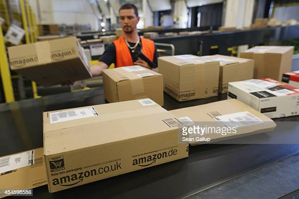 A worker prepares packages for delivery at an Amazon warehouse on September 4 2014 in Brieselang Germany Germany is online retailer Amazon's second...