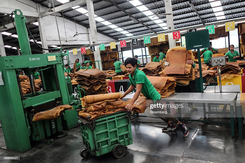 A worker prepares smoked rubber sheets to be packaged for shipment at the Thai Hua Rubber Pcl factory in Samnuktong, Rayong province, Thailand, on Wednesday, Jan. 29, 2014. Rubber production in Thailand, the world's largest exporter, may decline as growers from the main producing regions join protests seeking to overthrow the government, according to Von Bundit Co. Photographer: Dario Pignatelli/Bloomberg via Getty Images