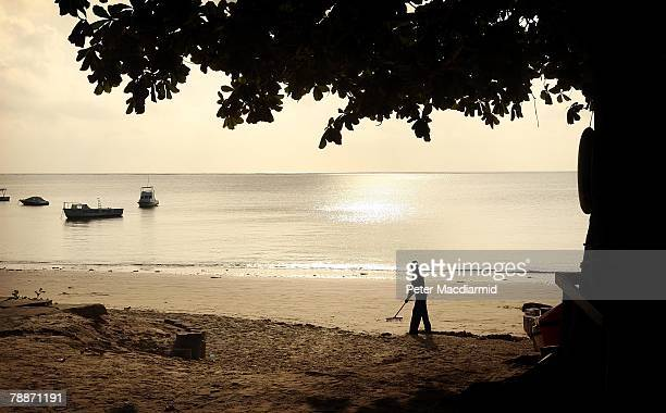 A worker prepares the beach near a private resort hotel on January 10 2008 in Mombasa Kenya Tourism is a $1 billion industry in Kenya Some tour...