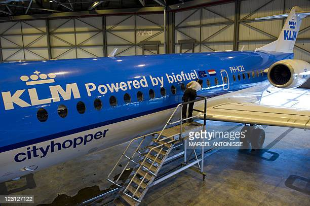A worker prepares the KLM Fokker 70 cityhopper airplane before its first flight using biofuel in Schiphol on August 31 2011 Dutch airline KLM...