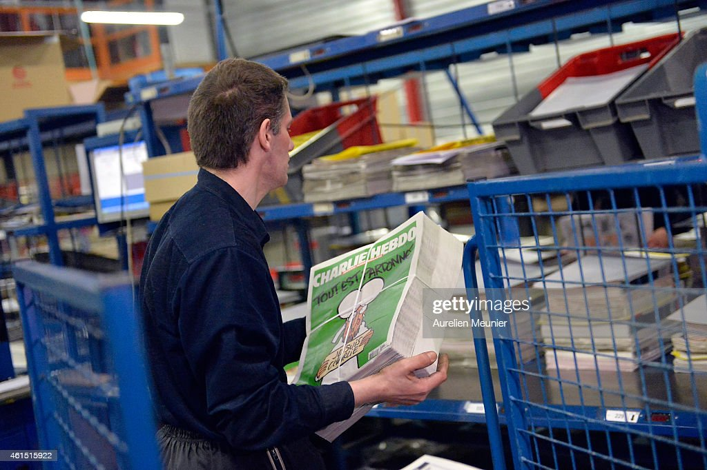A worker prepares the new edition of Charlie Hebdo for delivery in a press distribution center in the suburbs on January 14 2014 in MarnelaVallee...
