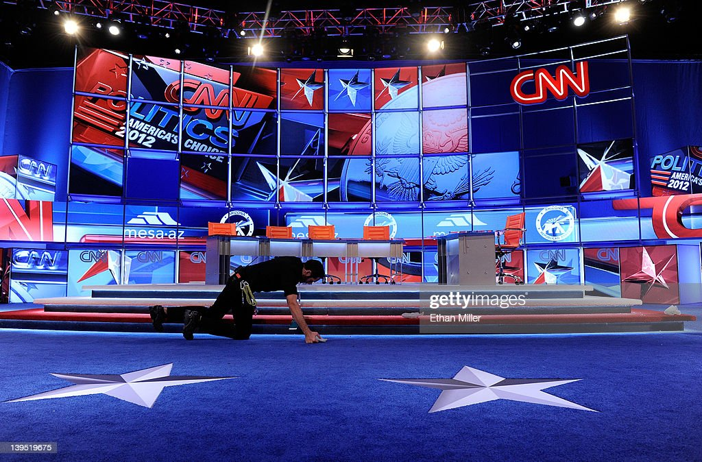 A worker prepares the stage for a debate sponsored by CNN and the Republican Party of Arizona at the Mesa Arts Center between Republican presidential...