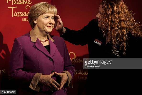 A worker prepares the three wax figures of German Chancellor Angela Merkel standing at Madame Tussauds on November 16 2015 in Berlin Germany The...