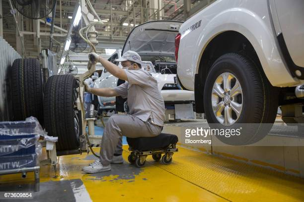 A worker prepares to fit a wheel onto a Nissan Motor Co Navara pickup truck on an assembly line at the company's plant in Samut Prakan Thailand on...