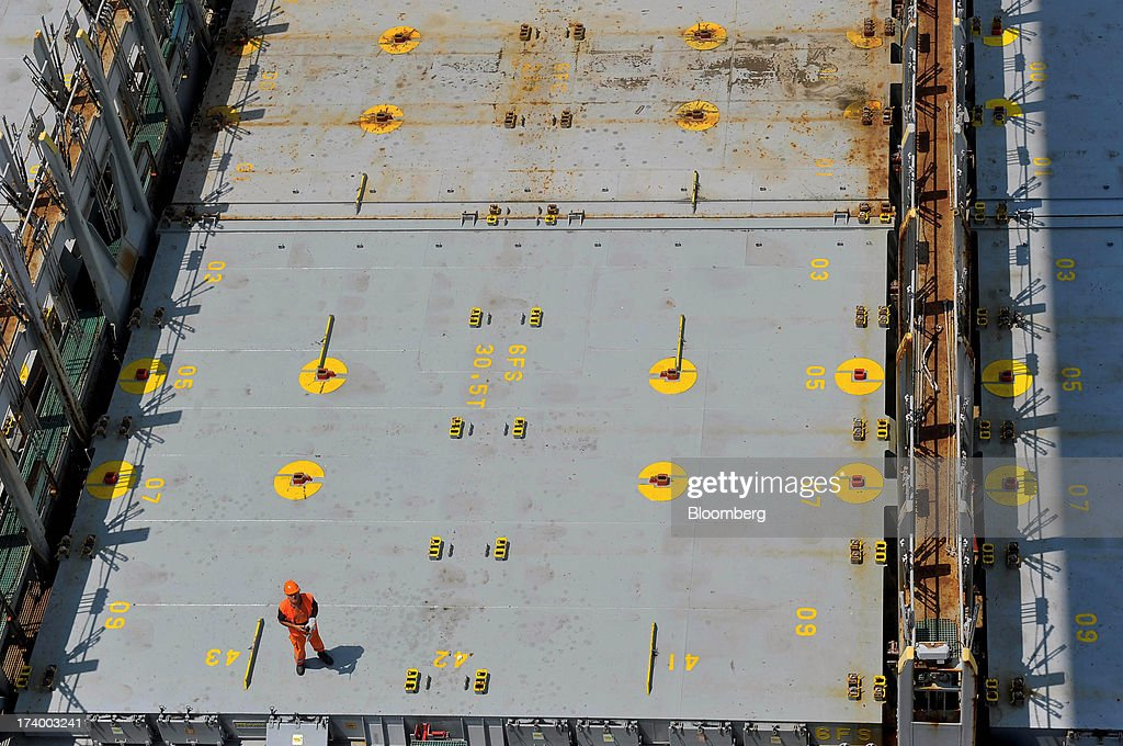 A worker prepares to guide a shipping container onto a ship at Thessaloniki Port, operated by Thessaloniki Port Authority SA, in Thessaloniki, Greece, on Thursday, July 18, 2013. Russian Railways is interested in buying Thessaloniki Port and Greek rail operator Trainose SA as one single unit, newspaper Real News reported, citing an interview with the Russian company's CEO Vladimir Yakunin. Photographer: Oliver Bunic/Bloomberg via Getty Images