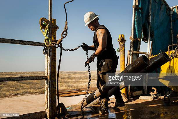 A worker prepares to lift drills by pulley to the main floor of Endeavor Energy Resources LP's Big Dog Drilling Rig 22 in the Permian basin outside...