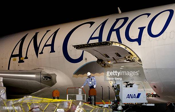 A worker prepares to load air containers onto an All Nippon Airways Co cargo aircraft at the company's cargo hub terminal at Naha Airport in Naha...