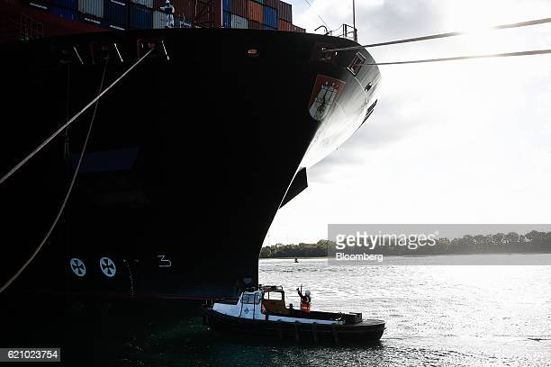 A worker prepares to receive ropes from the Ludwigshafen Express container vessel operated by HapagLloyd AG as it arrives on the dockside at the...