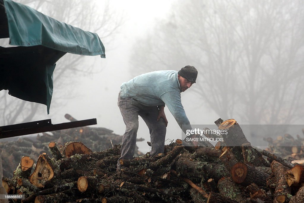 A worker prepares wood in a wood factory in Grevena, on January 2, 2013. Air pollution in cities of Greece has surged in recent days because of people choosing wood over more expensive fuels to heat their homes in the grips of a continuing economic crisis. Illegal logging has surged also in Greece as Forest Authorities reported that illegal logging activities across the country accounts for up to 30 percent of all lost forestland. AFP PHOTO /Sakis Mitrolidis