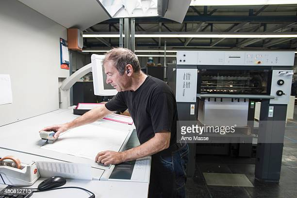 Worker preparing digital printing equipment in print workshop