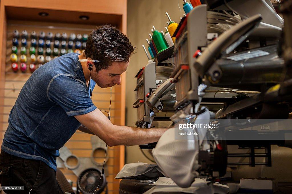 Worker preparing embroidery machine in t-shirt  printing workshop