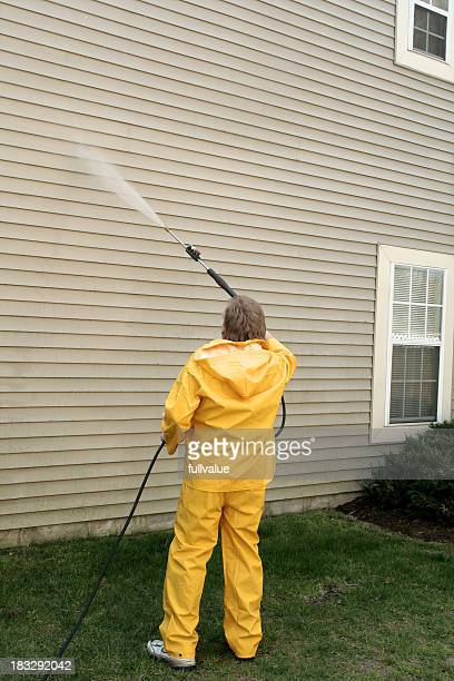 A worker pressure washing the siding of a house