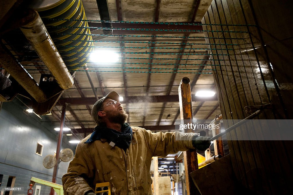 A worker pries apart multiple cuts in a block of sandstone to free the tension on a wire saw at the Cleveland Quarries facility in Vermilion, Ohio, U.S., on Friday, Feb. 1, 2013. Spending on U.S. construction projects climbed more than forecast in December, showing the housing industry is sustaining gains that may lift the economy. Photographer: Ty Wright/Bloomberg via Getty Images