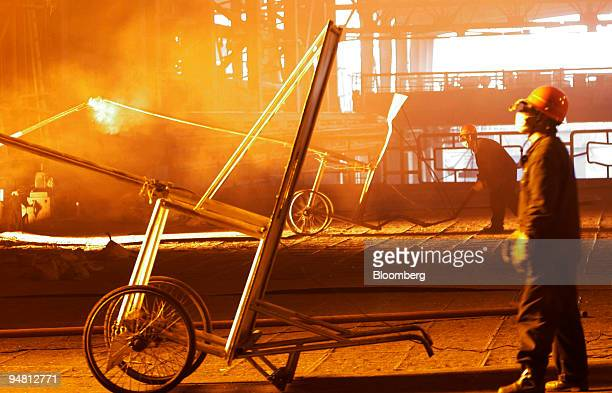 A worker protects himself with a shielded cart to retrieve samples from a steel smelter at Maanshan Iron Steel factory in Maanshan Anhui Province...