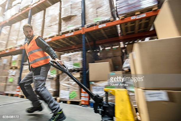 Worker pulling cardboard boxes on hand truck