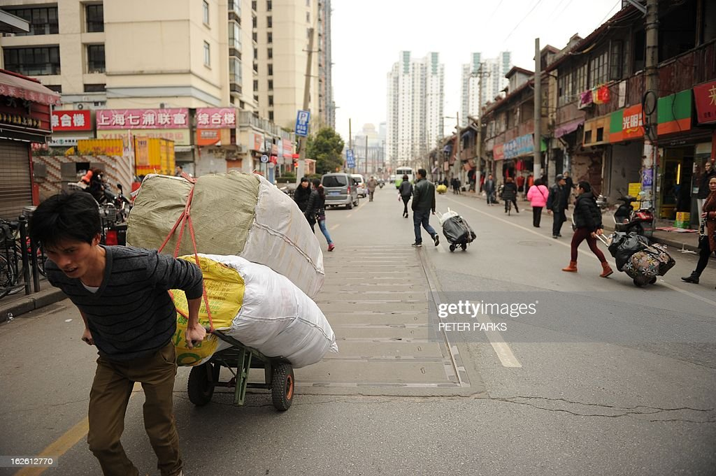 A worker pulls a cart outside a wholesale clothing market in Shanghai on February 25, 2013. China's manufacturing growth hit a four-month low in February but remained positive, British banking giant HSBC said on February 25, noting that the world's second-biggest economy was still recovering slowly. AFP PHOTO/Peter PARKS