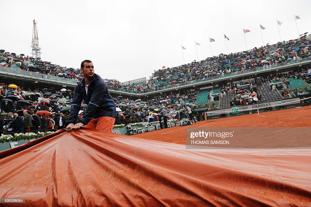 A worker pulls a tarp over the Philippe Chatrier court as rain interrupts play during the men's fourth round match between Japan's Kei Nishikori and France's Richard Gasquet at the Roland Garros 2016 French Tennis Open in Paris on May 29, 2016. / AFP / Thomas SAMSON
