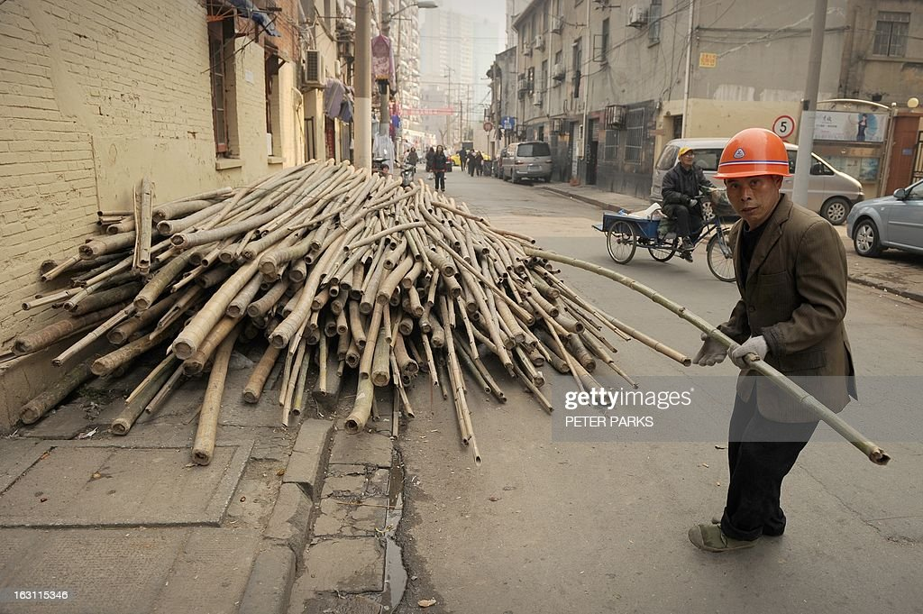 A worker pulls bamboo scaffolding on a street in Shanghai on March 5, 2013. Chinese Premier Wen Jiabao targeted 2013 growth of 7.5 percent and vowed an unwavering fight against corruption as the world's second-largest economy opened its annual parliamentary session. AFP PHOTO/Peter PARKS