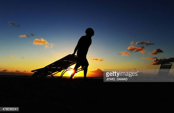 A worker pulls beach chairs back to store for the day as sun sets in Bridgetown on March 12 2014 AFP PHOTO/Jewel Samad