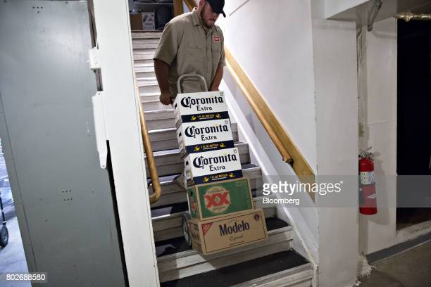 A worker pulls cases of Constellation Brands Inc Corona and Modelo beer up a staircase during a delivery in Ottawa Illinois US on Tuesday June 27...