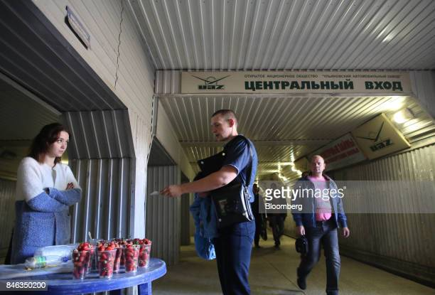 A worker purchases strawberries from a street vendor as he exits the Ulyanovsk Automobile Plant through an underground tunnel following a work shift...