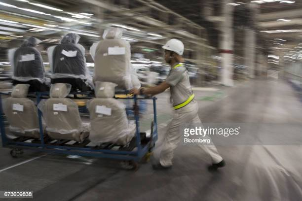 A worker pushes a cart loaded with Nissan Motor Co Navara pickup truck seats at the company's plant in Samut Prakan Thailand on Tuesday April 25 2017...