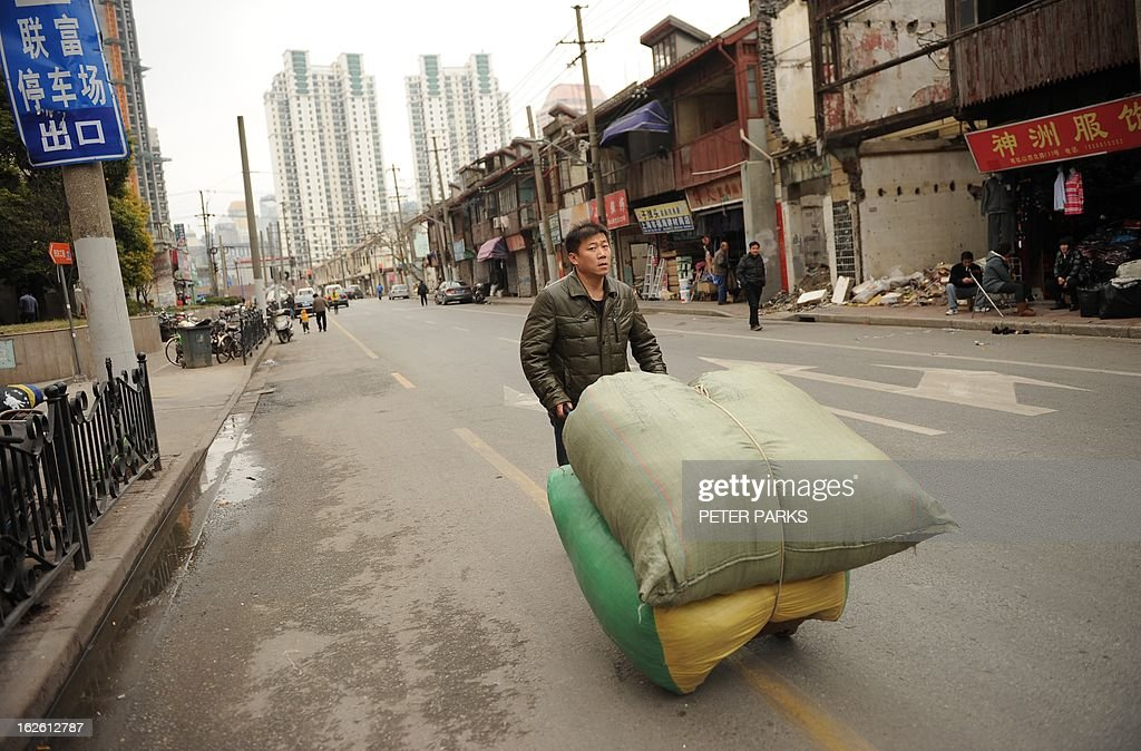 A worker pushes a cart outside a wholesale clothing market in Shanghai on February 25, 2013. China's manufacturing growth hit a four-month low in February but remained positive, British banking giant HSBC said on February 25, noting that the world's second-biggest economy was still recovering slowly. AFP PHOTO/Peter PARKS