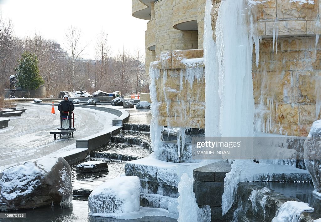 A worker pushes a cart past an ice and snow covered waterfall outside of the National Museum of the American Indian on January 24, 2013 in Washington, DC. A light blanket of snow fell over the Washington region, causing some school closures and delays. AFP PHOTO/Mandel NGAN