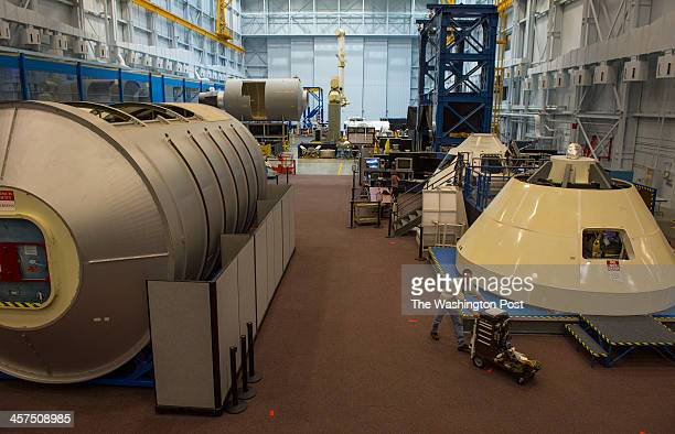 A worker pushes a cart past an Orion capsule mockup inside the Space Vehicle MockUp Facility at the Lyndon B Johnson Space Center on August 27 2013...