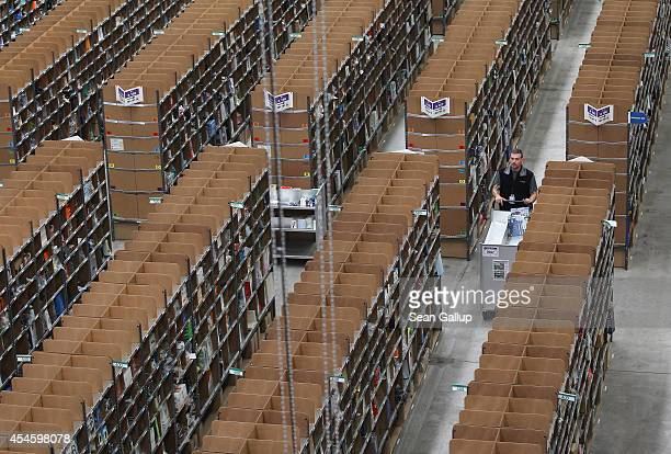 A worker pushes a cart through shelves lined with goods at an Amazon warehouse on September 4 2014 in Brieselang Germany Germany is online retailer...