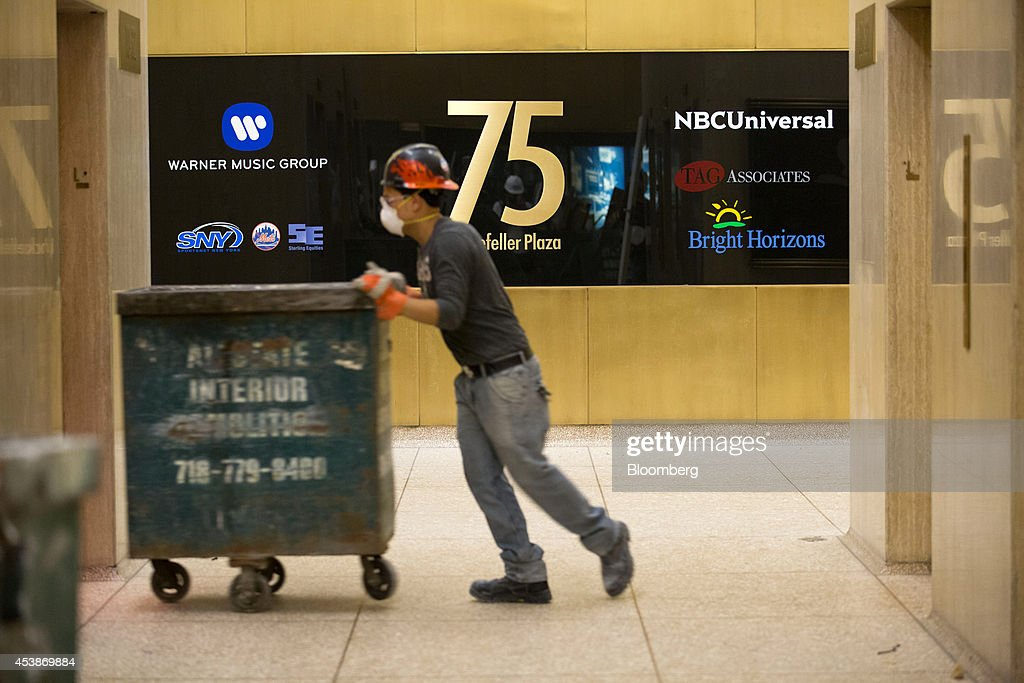 A worker pushes a crate for demolition work into an elevator in 75 Rockefeller Plaza during demolition ahead of renovations ahead of renovations in New York, U.S., on Monday, Aug. 18, 2014. New landlord RXR Realty Corp. is upgrading the entire 630,000 square feet. The $150 million project includes raising office ceilings from 7.5 feet (2.3 meters) to 9 feet, and relocating mechanical equipment from the top floor to create new high-priced space, said Scott Rechler, RXRís chief executive officer. Photographer: Jin Lee/Bloomberg via Getty Images