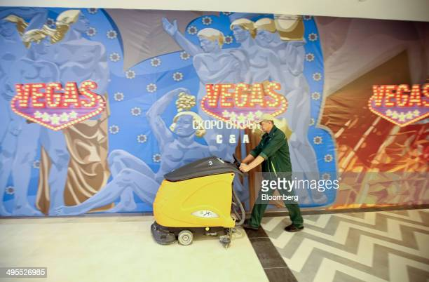 A worker pushes a floor polishing machine past billboards advertising a future CA store location inside the new Vegas shopping mall operated by...