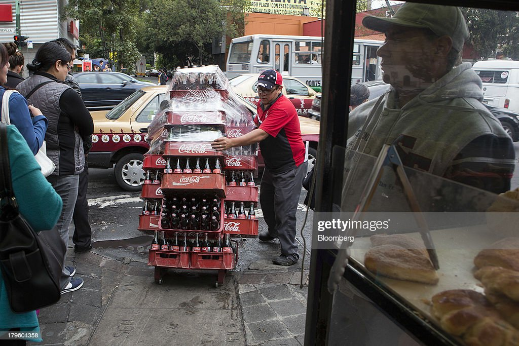 A worker pushes a hand truck filled with cases of Coca-Cola while making deliveries in Mexico City, Mexico, on Thursday, Sept. 5, 2013. Coca-Cola Femsa SAB, a bottler and distributor of Coca-Cola products in Mexico, agreed to buy Brazils Spaipa SA Industria Brasileira de Bebidas in a cash deal with a total transaction value of $1.86 billion. Photographer: Susana Gonzalez/Bloomberg via Getty Images
