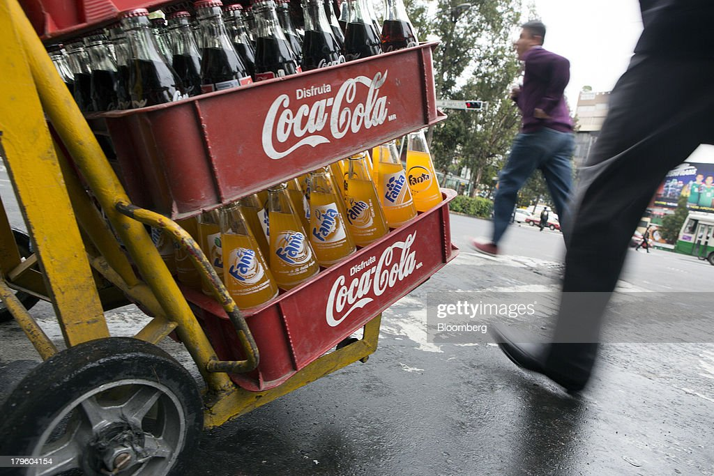 A worker pushes a hand truck with Coca-Cola products while making deliveries in Mexico City, Mexico, on Thursday, Sept. 5, 2013. Coca-Cola Femsa SAB, a bottler and distributor of Coca-Cola products in Mexico, agreed to buy Brazils Spaipa SA Industria Brasileira de Bebidas in a cash deal with a total transaction value of $1.86 billion. Photographer: Susana Gonzalez/Bloomberg via Getty Images